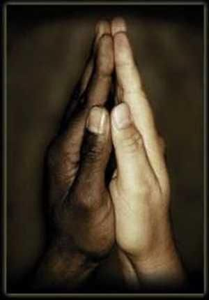 Black hand next to white hand in a prayer position